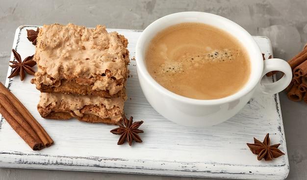 Pilha de biscoitos de merengue cracóvia assados em uma placa de madeira e um copo de cerâmico branco com café preto