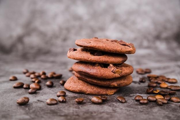 Pilha de biscoitos e grãos de café torrados no pano de fundo grunge