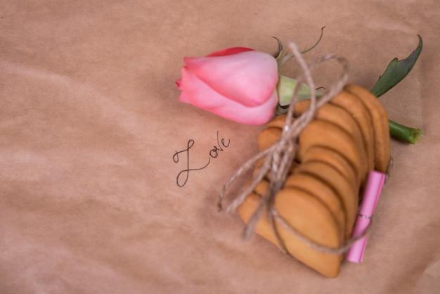 Pilha de biscoitos em forma de coração com rosa