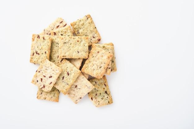 Pilha de biscoitos salgados de grãos com farelo e sementes de linho no fundo branco