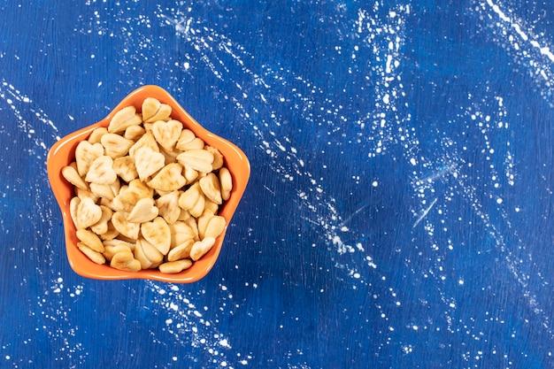 Pilha de biscoitos salgados em forma de coração colocados em uma tigela de laranja.