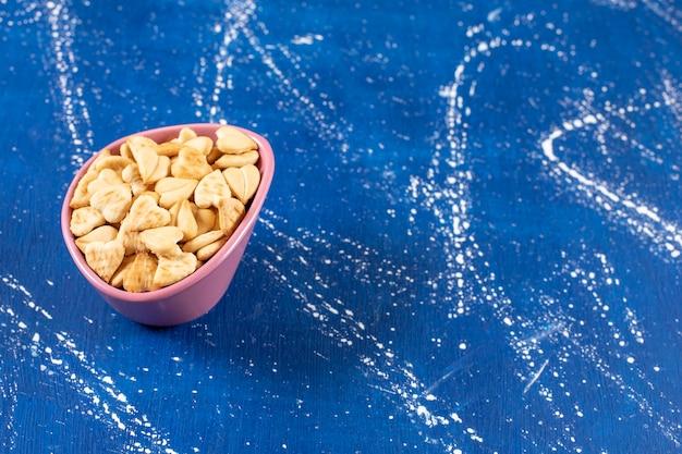 Pilha de biscoitos salgados em forma de coração colocados em uma tigela rosa.