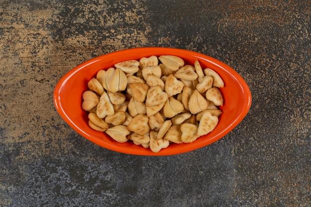 Pilha de biscoitos salgados em forma de coração em uma tigela de laranja.