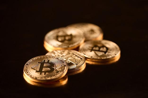 Pilha de bitcoins dourados como cryptocurrency principal do mundo isolado no fundo preto.