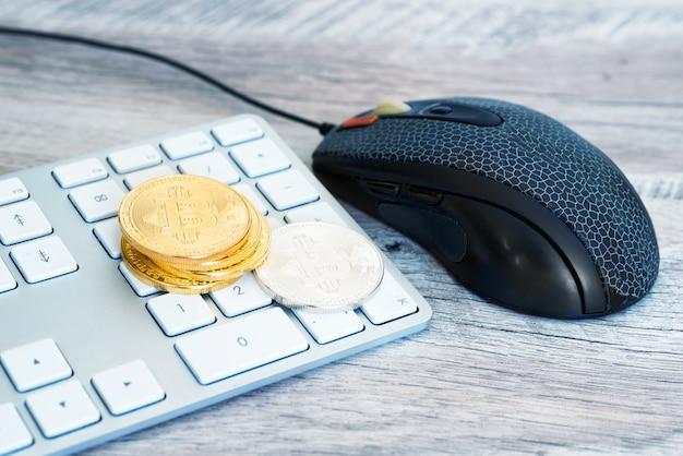 Pilha de bitcoins dourados e prateados em um teclado branco com mouse de computador. conceito de mineração de dinheiro eletrônico