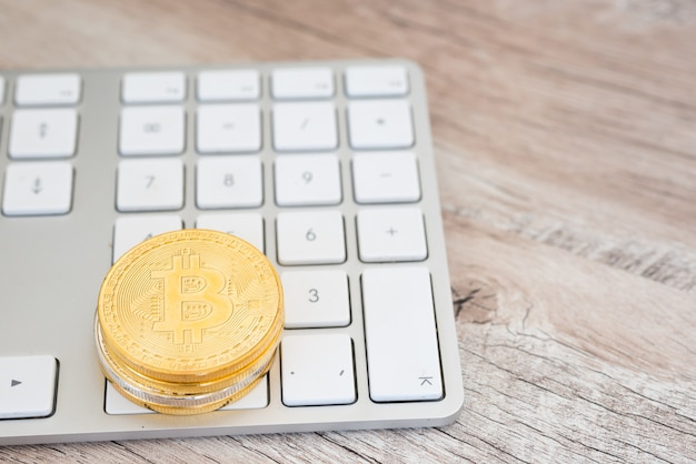Pilha de bitcoins dourados em um teclado branco