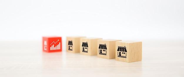 Pilha de blocos de madeira com ícones de lojas de franquias