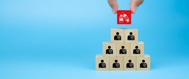 Pilha de blocos de madeira com seringa de vacina covid19 e proteção para pessoas com imunidade