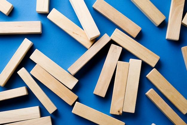 Pilha de blocos de madeira dispersos no azul.