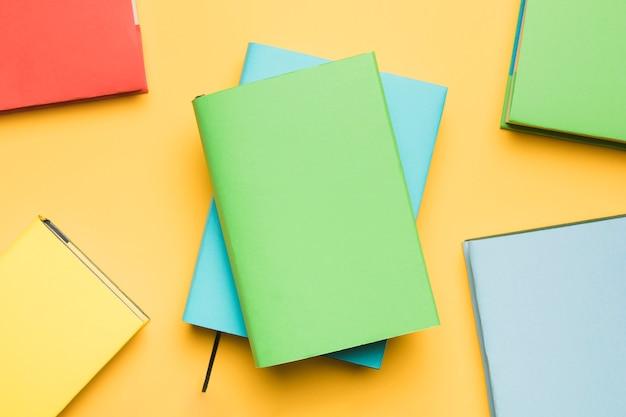 Pilha de blocos de notas, rodeados por livros coloridos