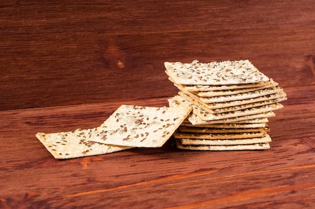 Pilha de bolos crocantes de trigo com sementes de gergelim, linho e girassol em uma mesa de madeira vermelha