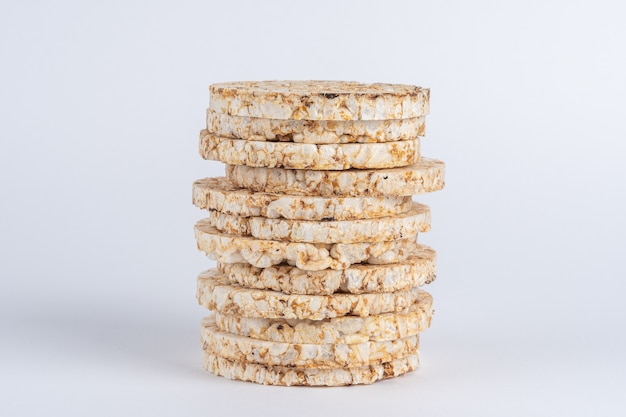 Pilha de bolos de arroz crocantes na mesa branca.