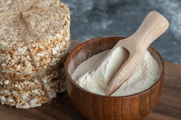 Pilha de bolos de arroz e tigela de farinha na placa de madeira