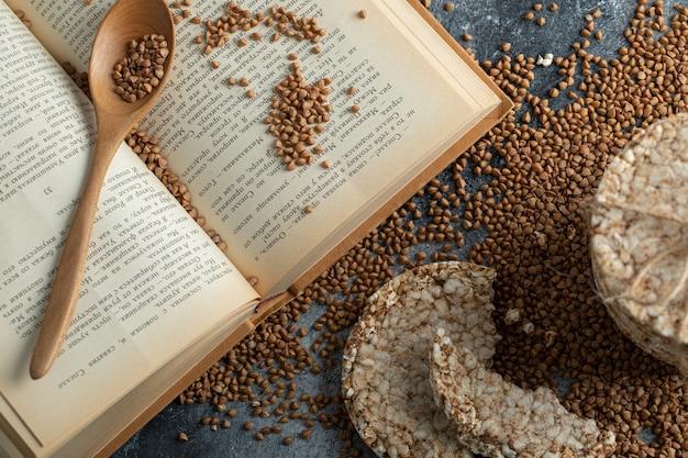 Pilha de bolos de arroz, livro e trigo sarraceno cru na superfície de mármore