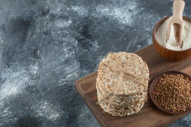 Pilha de bolos de arroz, tigela de farinha e trigo sarraceno na placa de madeira