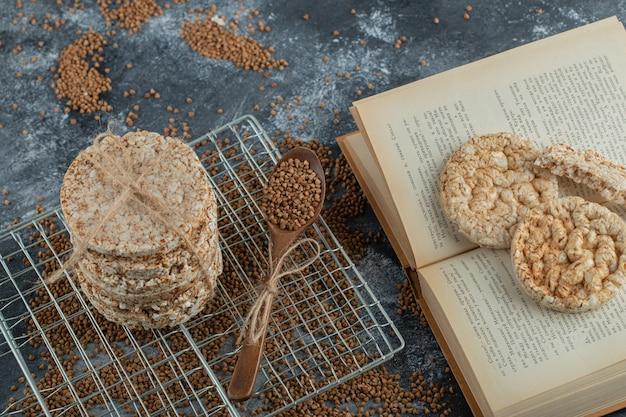 Pilha de bolos de arroz, trigo sarraceno e livro na superfície de mármore