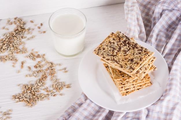 Pilha de bolos de trigo crocantes com linho de gergelim e sementes de girassol em um guardanapo sobre fundo branco de madeira com copo de leite