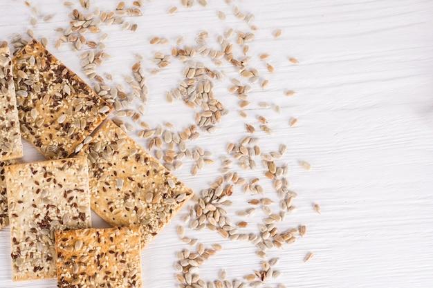Pilha de bolos de trigo crocantes com sementes de gergelim, linho e girassol em fundo branco de madeira. vista do topo. comida vegetariana,