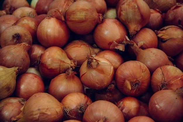 Pilha de bulbos de cebola vendida no mercado