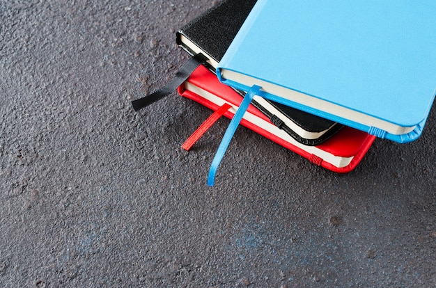 Pilha de cadernos coloridos para escrever ou livros sobre fundo escuro