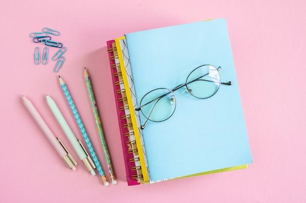 Pilha de cadernos com óculos no topo e grupos de clipes, canetas e lápis próximos no fundo rosa