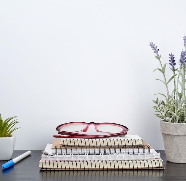 Pilha de cadernos de espiral ao lado de um pote de cerâmica com uma flor em uma mesa preta