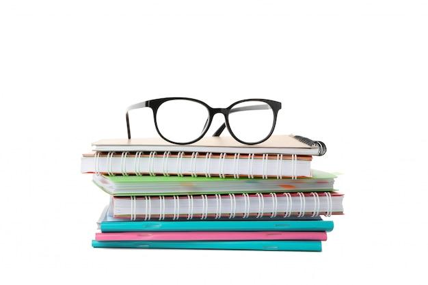 Pilha de cadernos e óculos isolados