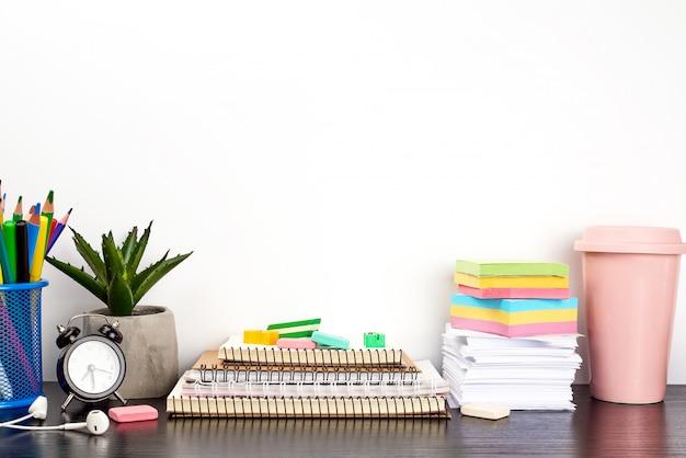 Pilha de cadernos em espiral e adesivos coloridos, ao lado de um vaso de cerâmica com uma flor