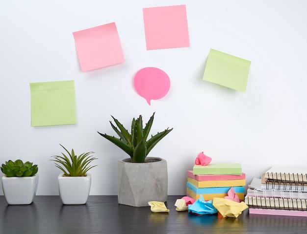 Pilha de cadernos em espiral e adesivos coloridos, ao lado de uma panela de cerâmica com uma flor