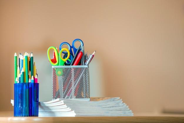 Pilha de cadernos, lápis coloridos do desenho e arranjo dos artigos de papelaria no espaço da cópia.