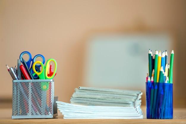 Pilha de cadernos, lápis de desenho coloridos e arranjo de artigos de papelaria