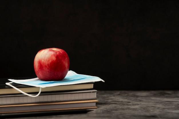 Pilha de cadernos, maçã vermelha e máscara médica protetora de rosto.