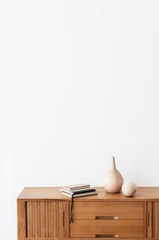 Pilha de cadernos perto de um vaso de madeira em um armário de madeira em uma sala branca
