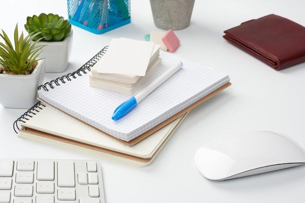 Pilha de cadernos, plantas verdes em vasos e um mouse, local de trabalho de um freelancer