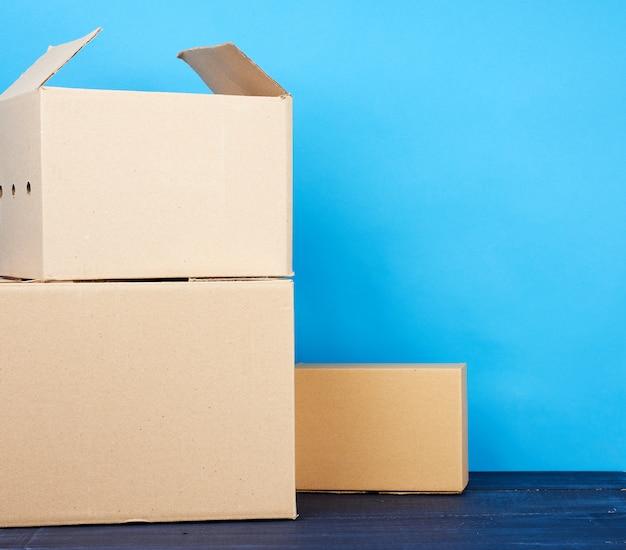 Pilha de caixas de papelão de papel kraft marrom sobre uma mesa de madeira azul