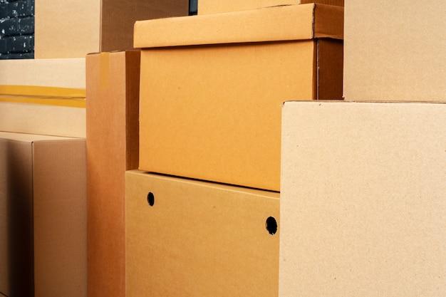 Pilha de caixas de papelão na sala vazia contra a parede de tijolos pretos