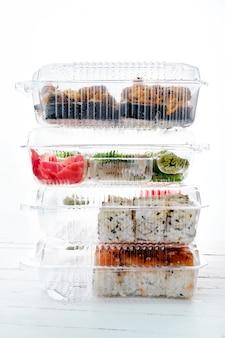 Pilha de caixas de plástico com conjuntos de rolo de sushi