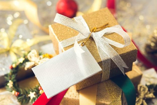 Pilha de caixas de presente de natal brilhante com itens de decoração na mesa