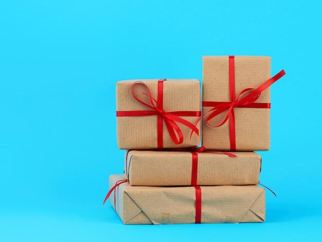 Pilha de caixas embrulhadas em papel pardo e amarradas com um laço vermelho, presentes em azul