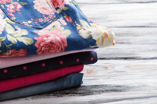 Pilha de calças dobradas, pontilhadas escuras e calças florais com estampa de flores na roupa da senhora, compre e economize