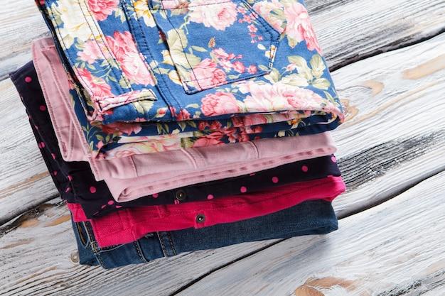 Pilha de calças rosa e jeans casuais de materiais coloridos de qualidade para calças dobradas e desi ...