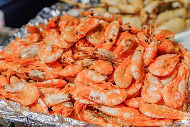 Pilha de camarões cozidos no mercado. frutos do mar de rua