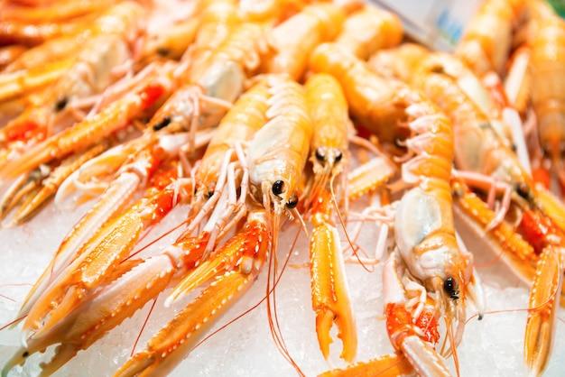 Pilha de camarões vermelhos frescos no mercado. textura de frutos do mar para o fundo