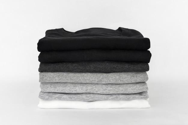 Pilha de camiseta preta, cinza e branca dobrada