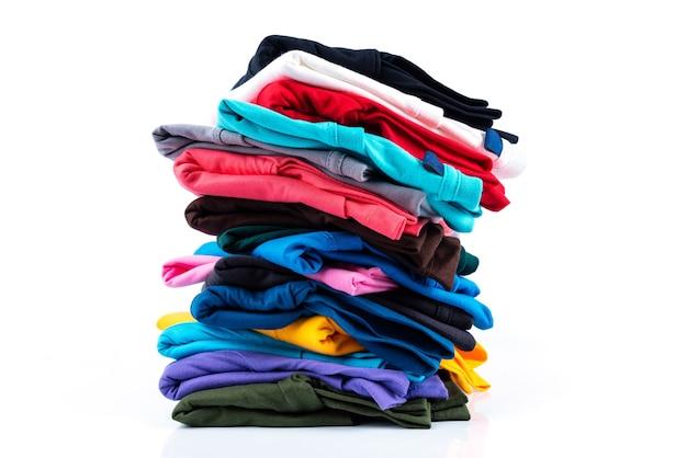 Pilha de camisetas de algodão coloridas isoladas no fundo branco.