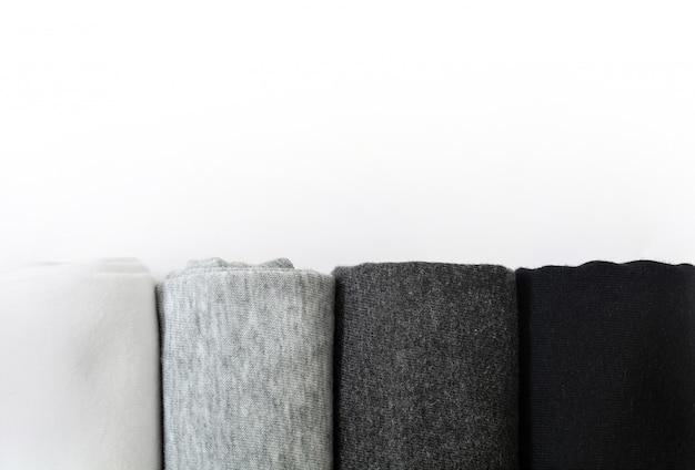 Pilha de camisetas pretas, cinza e brancas