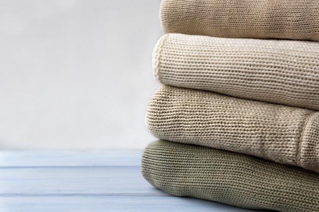 Pilha de camisolas de lã tricotadas na mesa de madeira clara.
