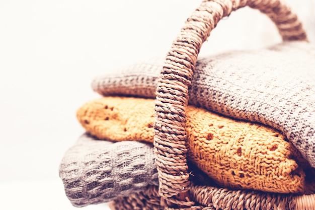 Pilha de camisolas de malha acolhedoras na cesta de vime