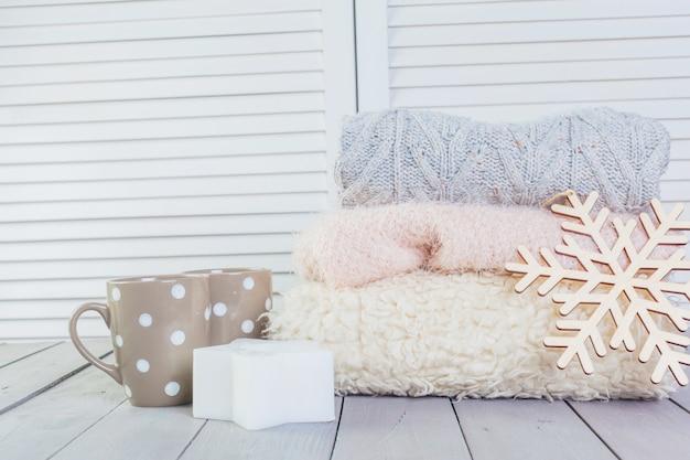 Pilha de camisolas de malha aconchegantes brancas sobre uma mesa de madeira