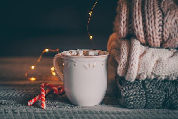 Pilha de camisolas de malha aconchegantes e xícara de chocolate quente com marshmallow